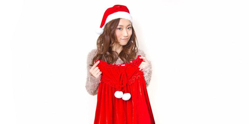 サンタのコスプレ衣装を持つ女性